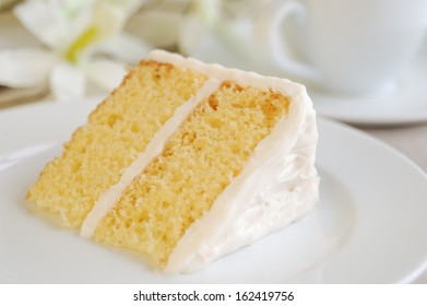 Piece of yellow cake with vanilla frosting on elegant table.