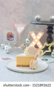 Piece of yellow mango cheesecake decorated with macaron on the top. Located on grey background with party decorations, grey cakestand and lamp garland