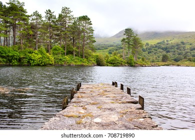 Pieceful view of the stone jetty on the lake with forest and montains on the backgound somewhere in Ireland.