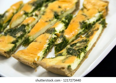 Pieces asparagus pie with eggs on a white porcelain plate.