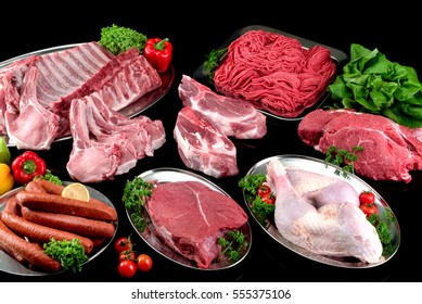 Pieces of assorted raw meat,poultry and sausages on inox plates, black background.