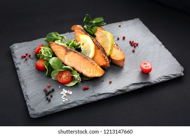 Pieces of baked salmon on lettuce. Dinner dish on a black plate.