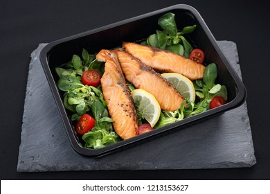 Pieces of baked salmon on lettuce. Ready take-away dish packed in a lunch box