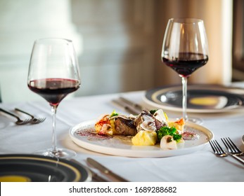 Pieces of beef meat, steaks with different sauces and decorative elements with red wine, restaurant kitchen, horizontal
