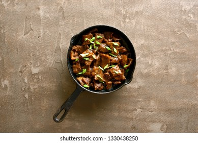 Pieces of beef stewed in soy sauce with spices in asian style on brown background with copy space. Top view, flat lay