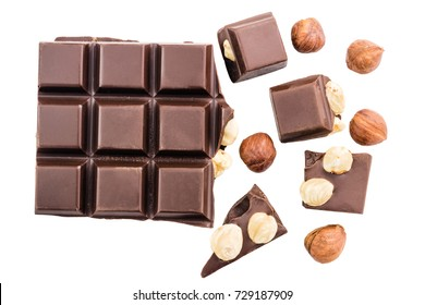 Pieces of bitter dark chocolate cubes with hazelnut isolated on white background, top view.