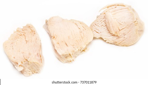 Pieces of boiled chicken breast over white background.