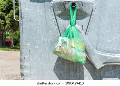 Pieces of bread in the plastic or nylon bag left on the metal garbage dumpster can on the street in the city for poor hungry or homeless people to take to eat