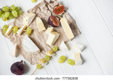 pieces of brie cheese and camembert on a white wooden table, with fruits grapes and fig. top view