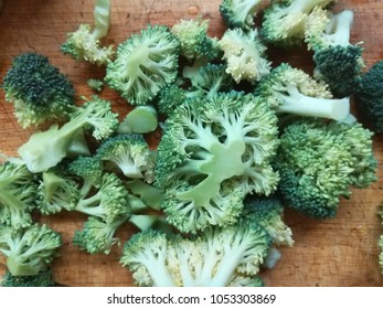 Pieces of broccoli at wooden background