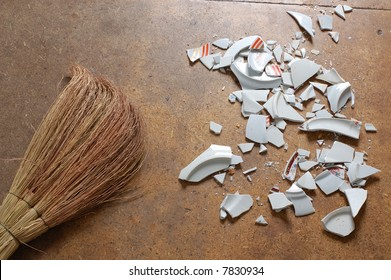 pieces of broken dish and a besom, laying on the floor
