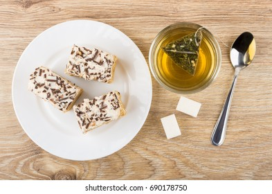 Pieces of cakes with cream and chocolate chips, tea and sugar on wooden table. Top view