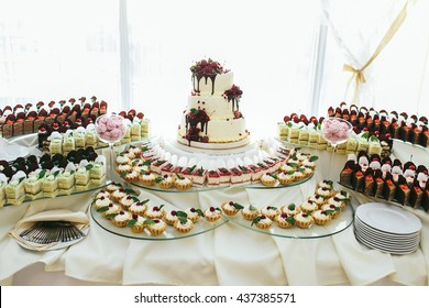Pieces of cakes surround white wedding cake on a dinner table