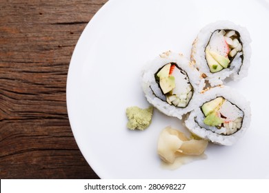 Pieces of California roll sushi on a white plate.