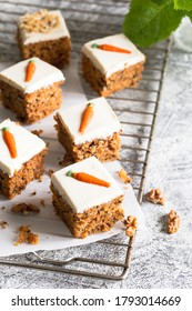 pieces of carrot cake with walnuts with icing cream on a light background. tinting. selective focus/