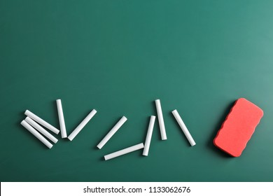 Pieces of chalk and blackboard duster on green background, top view