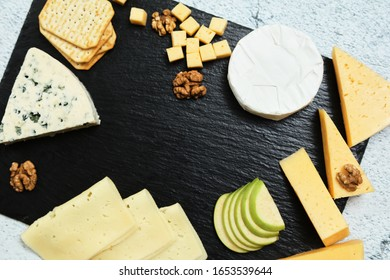 Pieces of cheese on a dark background. Cheeseboard. Sliced ​​apple and nuts on the board. Hard cheese, camembert, roquefort, emmental.
