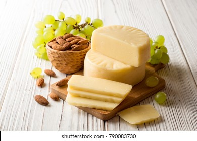 Pieces of cheese on wooden board with almonds and green grape on white wooden background. Selective focus.