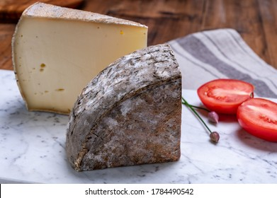 Pieces of cheese tomme de montagne or tomme de savoie made from cow milk in French Alps.