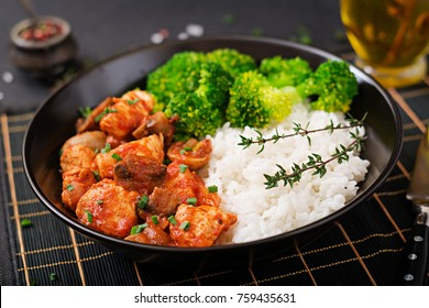 Pieces of chicken fillet with mushrooms stewed in tomato sauce with boiled broccoli and rice. Proper nutrition. Healthy lifestyle. Dietetic menu.