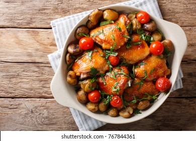 Pieces of chicken fried with chestnuts and tomatoes close-up in a bowl on the table. horizontal top view from above