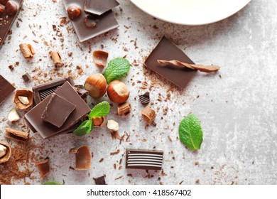 Pieces of chocolate with hazelnuts and fresh mint on light background