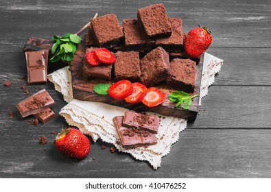 Pieces of chopped chocolate cake brownie with nuts, chocolate bars, leaves and sprigs of mint, strawberry berries on a cutting board on a black wooden background