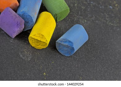 pieces of artist�´s colored pastels on black paper surface, macro