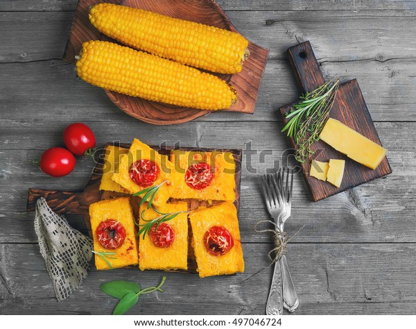 Pieces Corn polenta baked with cherry tomatoes, Parmesan cheese on board. Boiled corn on wooden plate for polenta. Green for corn polenta thyme, rosemary. Gray wooden background. Top view