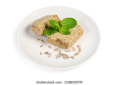 Pieces of the crumbly halva made with sunflower seeds, sugar and crushed peanuts, decorated with mint leaves, peeled sunflower seeds on the white dish on a white background