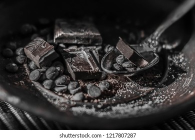 Pieces and crumbs of dark bitter chocolate are scattered on a plate and a spoon. Close-up. Dark brown background.