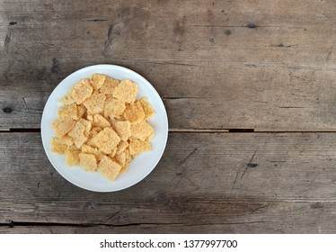 Pieces of crunchy dry Frico in a white plate on weathered wooden table. It is a traditional Friulian snack. Background for copy space