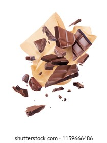 Pieces of crushed chocolate are fly out of a paper wrapper, isolated on white background