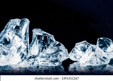 Pieces of crushed ice cubes on glossy black surface. Clipping path included.