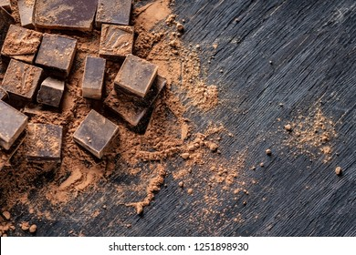 Pieces of dark bitter chocolate with cocoa powder on dark wooden background. Card with space for text
