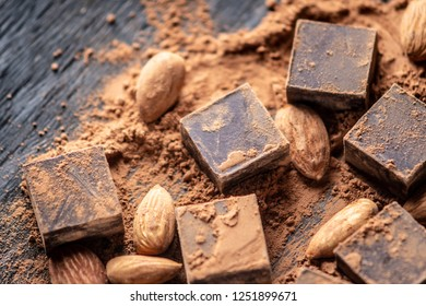 Pieces of dark bitter chocolate with cocoa powder and almonds nuts on wooden background. Card with space for text