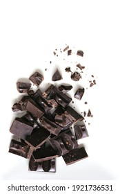 Pieces of dark chocolate bar on a light background. Top view, flat lay, copy space.