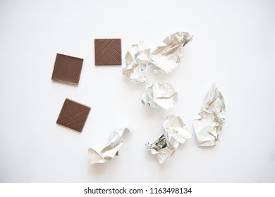 Pieces of dark chocolate with crumpled wrappers on white background.