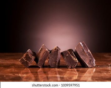 Pieces dark chocolate on a marble brown background