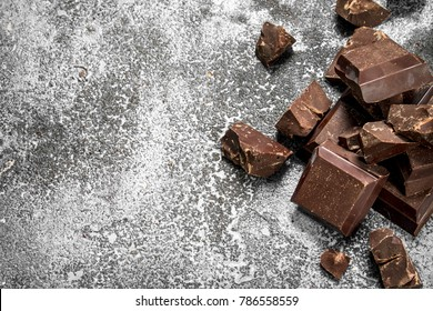 Pieces of dark chocolate. On a rustic background.