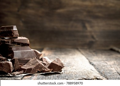 Pieces of dark chocolate. On a wooden background.