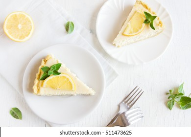 Pieces of delicious homemade lemon cheesecake with slices of lemon and mint on white background with copy space