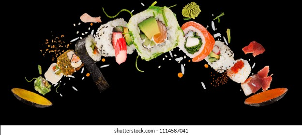 Pieces of delicious japanese sushi frozen in the air. Isolated on black background