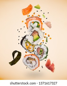 Pieces of delicious japanese sushi frozen in the air on pastel color background.