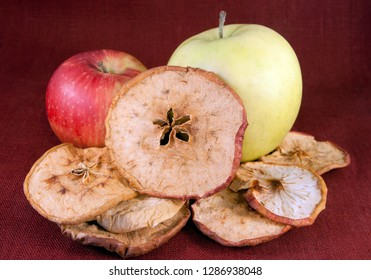 Pieces of dried apple and two fresh red and green apples