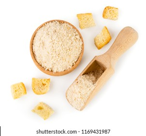 Pieces of dried bread and breadcrumbs in a wooden plate and spoon on a white. Isolated, top view.