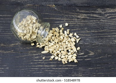Pieces of dried  root marshmallow in a glass bottle