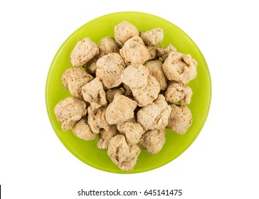Pieces of dry soy meat in green bowl isolated on white background. Top view