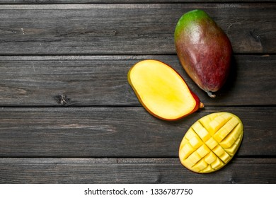 Pieces of fragrant mango. On black wooden background