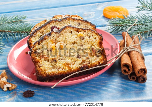 Pieces of fresh baked homemade fruitcake for Christmas on plate and spruce branches on boards, delicious dessert concept